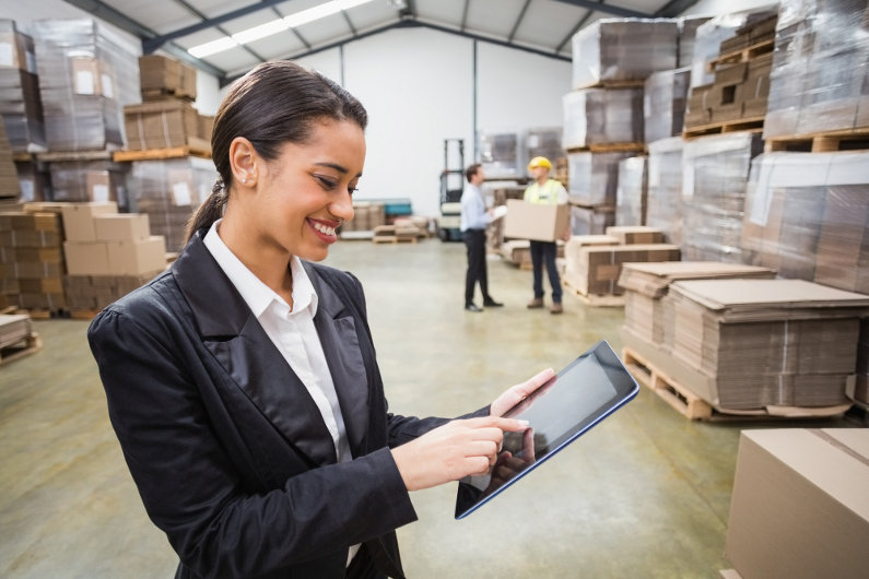 Supply chain manager using tablet PC in warehouse