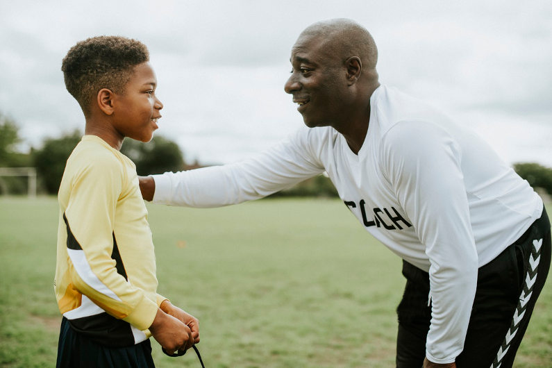 Senior sport coach advising young boy