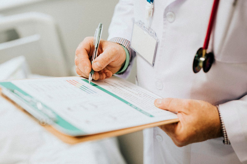 Physician taking notes on a patient's condition
